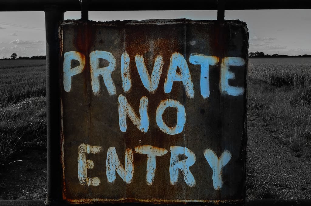 "A wooden sign with the words ""Private no entry"" painted on"