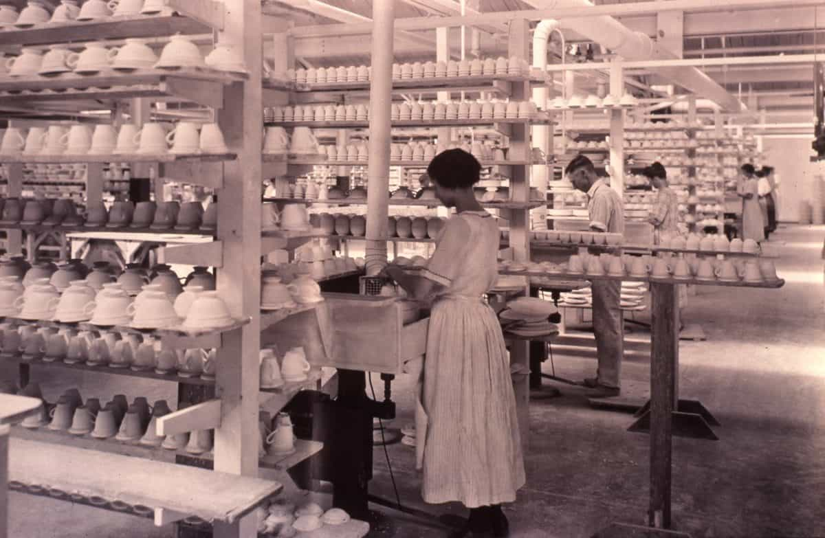 woman in white dress among shelves of unfired pots