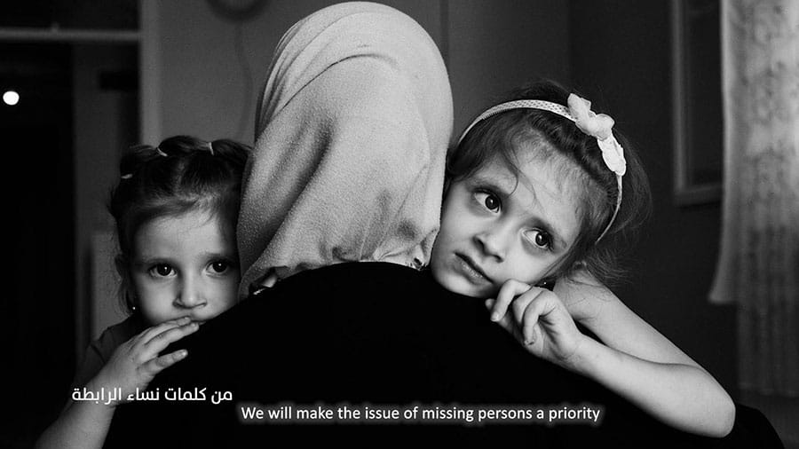 A still from one of the exhibits from In Their Absence, a woman in a headscarf hugs two children, both look worried
